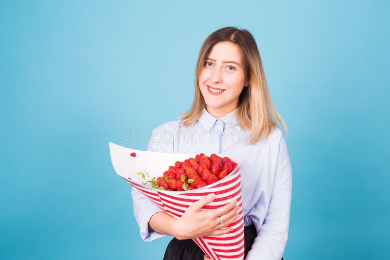 Ramo de fresas en las manos de una muchacha en fondo azul fotos de archivo