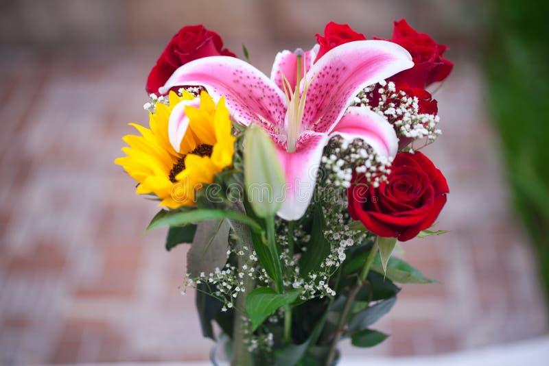 Ramo de girasoles, de lirio y de rosas en un florero fotos de archivo