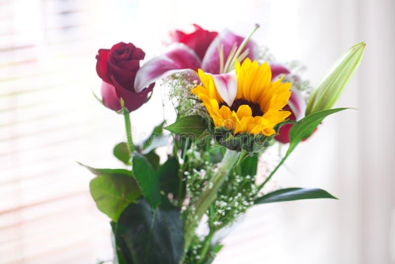 Ramo de girasoles, de lirio y de rosas en un florero fotos de archivo libres de regalías