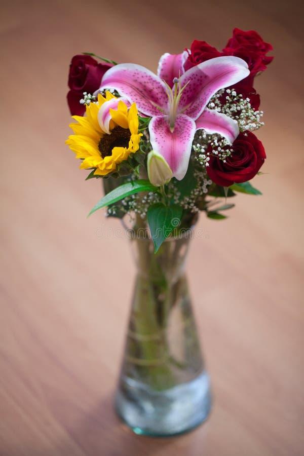 Ramo de girasoles, de lirio y de rosas en un florero fotografía de archivo