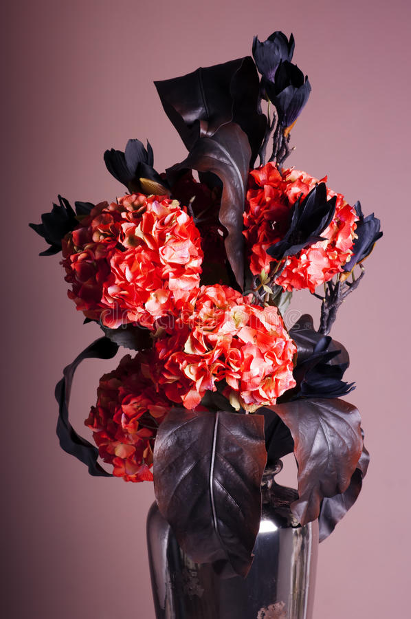 Ramo de hortensia roja y de magnolia azul marino en un florero imagen de archivo
