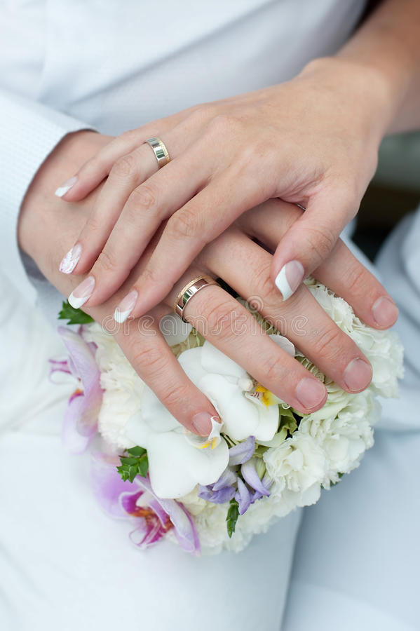Ramo de la boda con las manos y los anillos fotografía de archivo