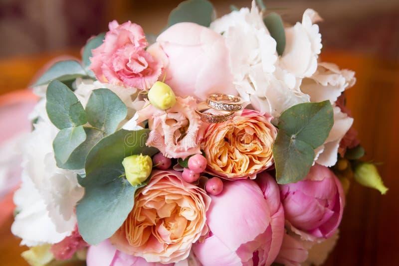 Ramo de la boda con las peonías y los anillos de oro dentro imagen de archivo