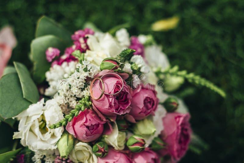 Ramo de la boda con los anillos en la hierba foto de archivo
