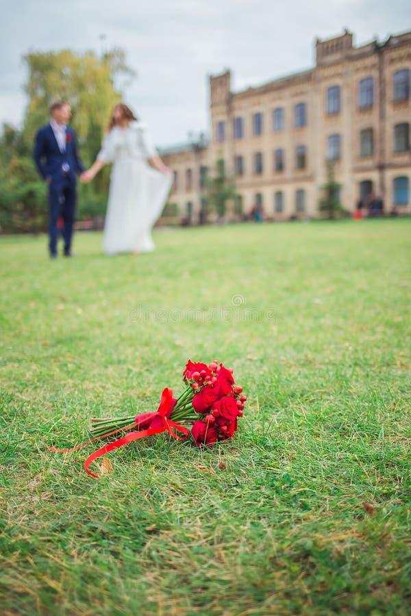 Ramo de la boda en la hierba y los recienes casados fotografía de archivo libre de regalías
