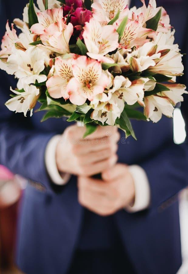 Ramo de la boda en las manos del novio foto de archivo
