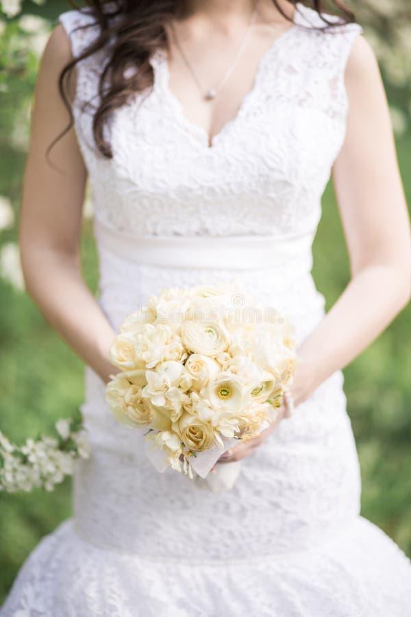Ramo de la boda en manos del ` s de la novia fotos de archivo