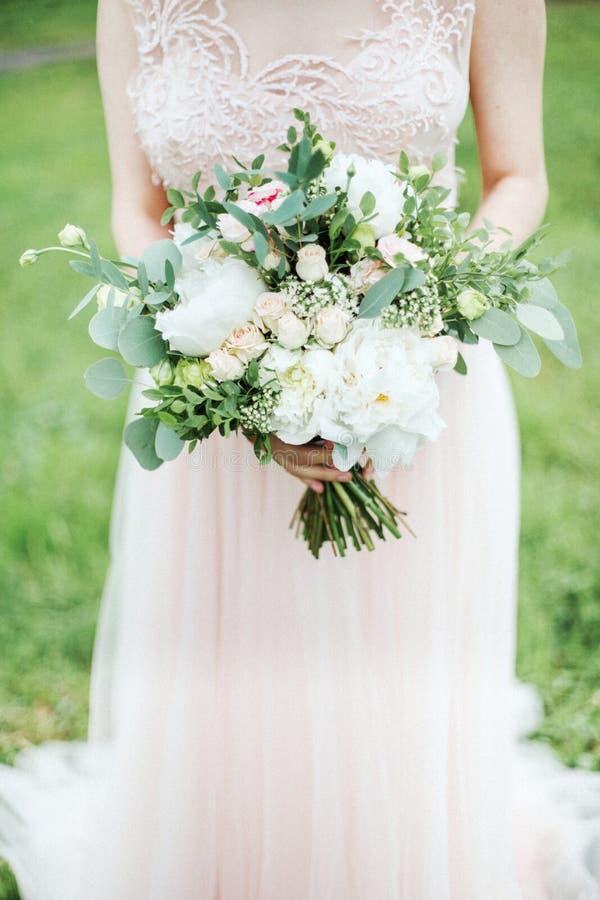 Ramo de la boda en manos del ` s de la novia imagen de archivo