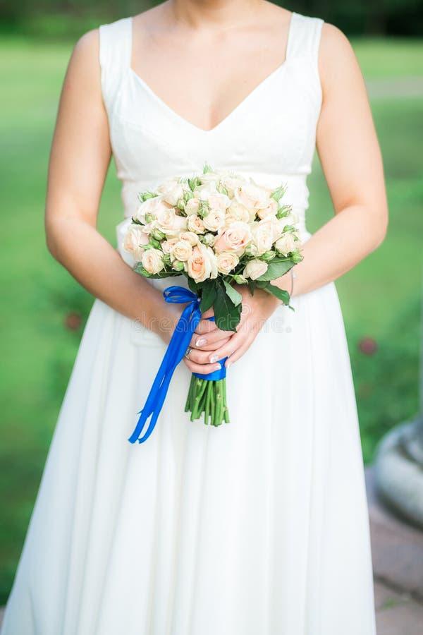 Ramo de la boda en manos del ` s de la novia imágenes de archivo libres de regalías
