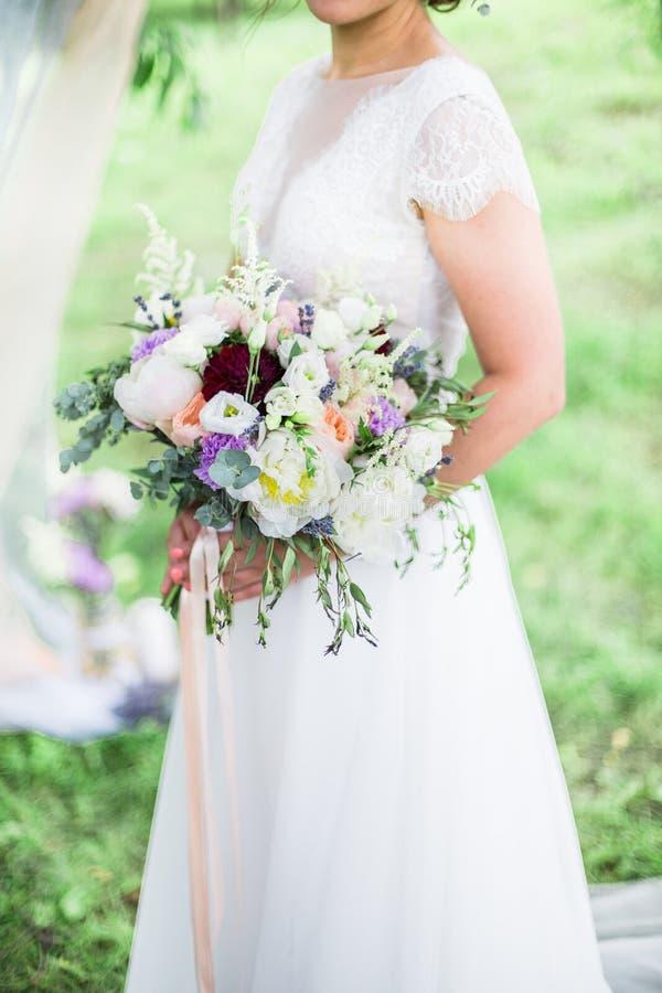 Ramo de la boda en manos del ` s de la novia fotos de archivo libres de regalías
