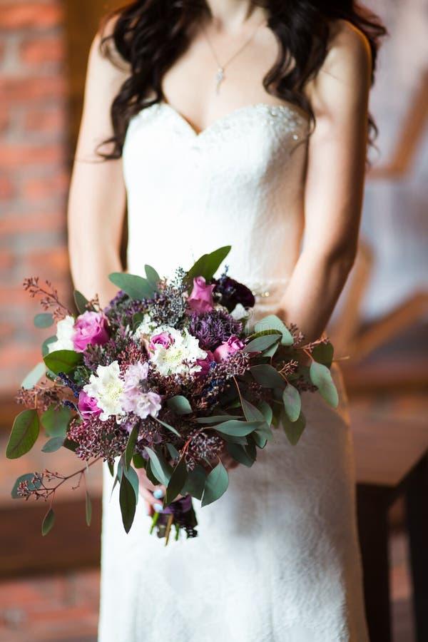 Ramo de la boda en manos del ` s de la novia foto de archivo libre de regalías