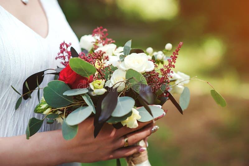Ramo de la boda en manos del ` s de la novia Día de boda Ramo nupcial de moda Ramo hermoso de flores rojas Flores hermosas en muc foto de archivo libre de regalías