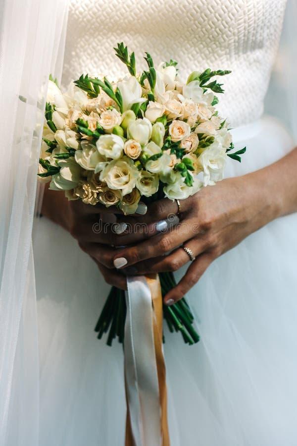 Ramo de la boda en manos del ` s de la novia Manojo de pequeñas flores elegantes fotografía de archivo libre de regalías
