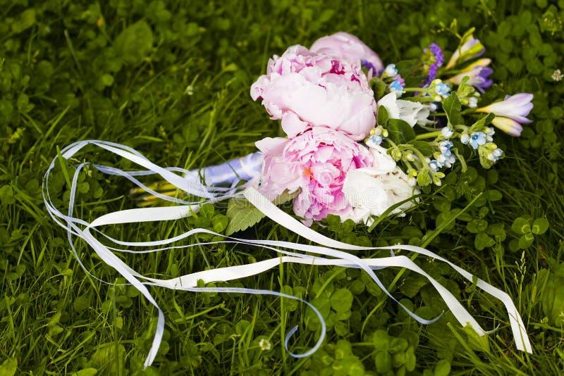 Ramo de la boda de flores rosadas, violetas y azules en hierba verde imagen de archivo