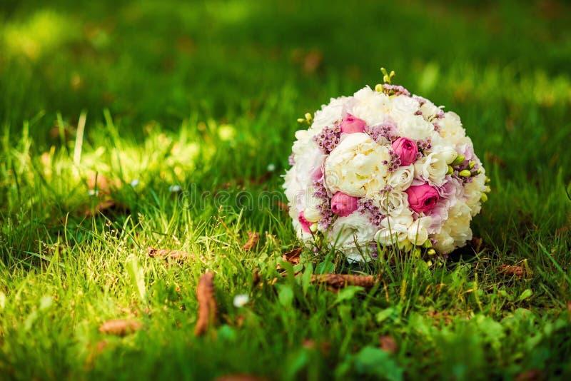 Ramo de la boda de flores rosadas y blancas delicadas que mienten en hierba verde Concepto de la boda fotos de archivo
