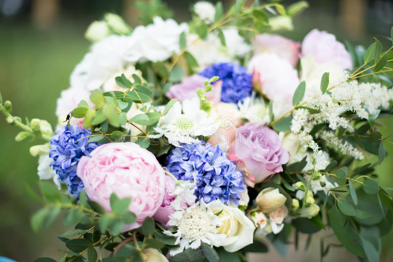 ramo de la boda de flores y de verdor púrpuras en el fondo de la hierba verde foto de archivo