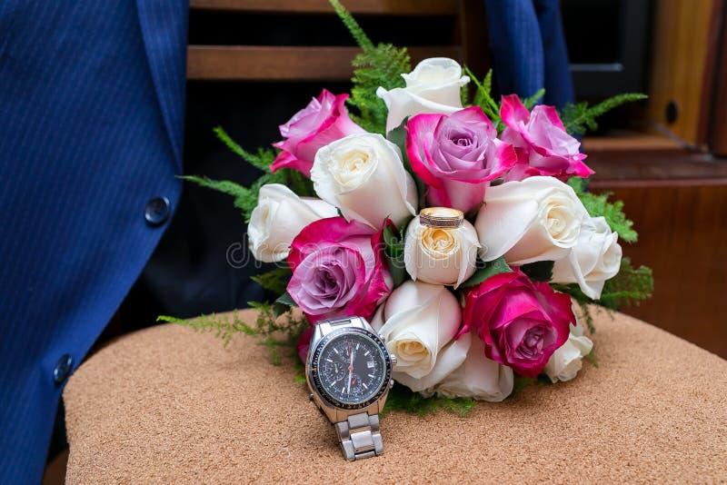 Ramo de la boda de rosas blancas y rosadas que mienten en una silla contra una chaqueta azul fotografía de archivo