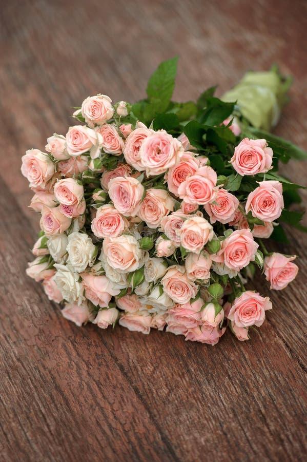 Ramo de la boda de rosas del rosa y blancas que mienten en piso de madera fotografía de archivo