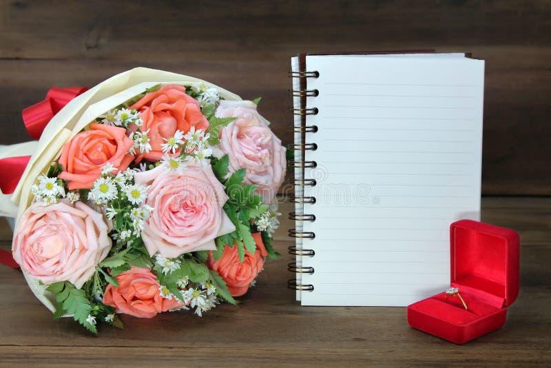 Ramo de la boda de rosas rosadas y anaranjadas, del anillo de bodas y de un libro blanco para el espacio de la copia en fondo de  foto de archivo
