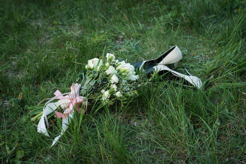 Ramo de la boda Zapatos beige y negros de la moda femenina de la boda con el ramo del ` s de la novia de rosas blancas y de verdo imagenes de archivo
