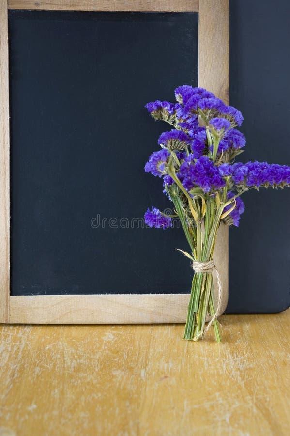 Ramo de la flor puesto al lado de la pizarra imágenes de archivo libres de regalías