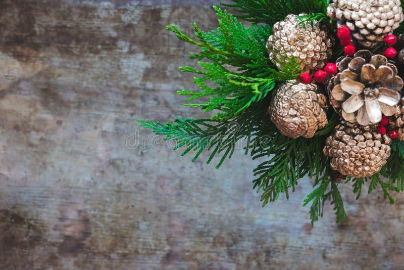 Ramo de la Navidad con los conos de oro del pino, las bayas rojas y árbol de hoja perenne en fondo de madera fotografía de archivo