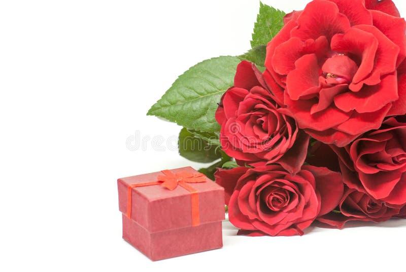 Ramo de las rosas rojas y pequeña caja del anillo de compromiso de la boda en el concepto blanco de la oferta del espacio fotografía de archivo libre de regalías