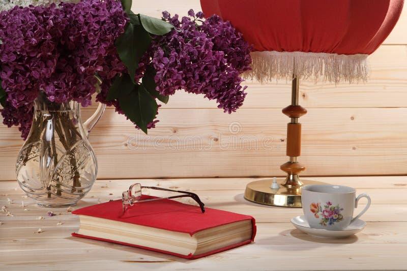 Ramo de lilas, de libro, de gafas, de taza de té y de lámpara de mesa fotografía de archivo