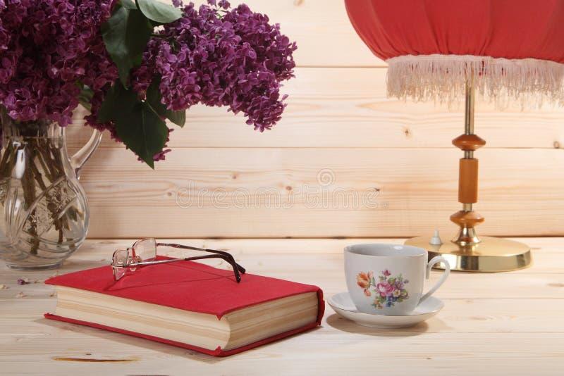 Ramo de lilas, de libro, de gafas, de taza de té y de lámpara de mesa imagen de archivo