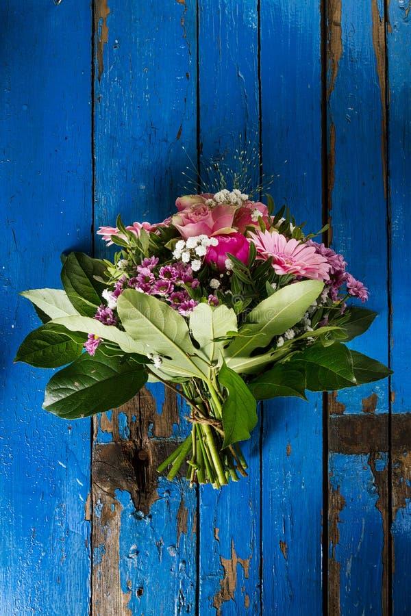 Ramo de los colores en colores pastel de Beautifu en la tabla vieja rústica azul el top compite imagen de archivo
