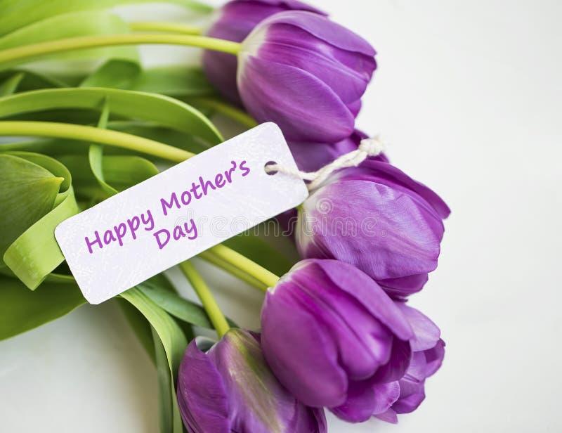 Ramo de los tulipanes de la primavera con la etiqueta de la tarjeta del día de madre, las mujeres o el saludo felices del día de  foto de archivo libre de regalías