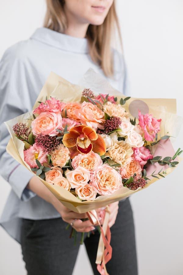 Ramo de lujo hermoso de flores mezcladas en mano de la mujer el trabajo del florista en una floristería Una pequeña familia fotos de archivo libres de regalías