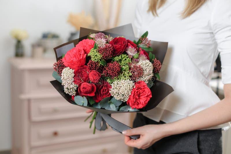 Ramo de lujo hermoso de flores mezcladas en mano de la mujer el trabajo del florista en una floristería Una pequeña familia foto de archivo