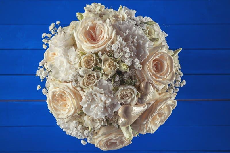 Ramo de marfil de la boda de rosas en el fondo de madera azul, arreglo floral en el color en colores pastel, celebración fotografía de archivo libre de regalías