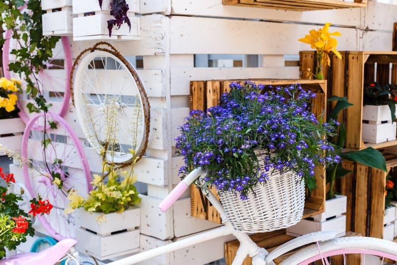 Ramo de muchas pequeñas flores azules en cesta de mimbre de la bicicleta, adornado en estilo de madera, diseño floral fotografía de archivo