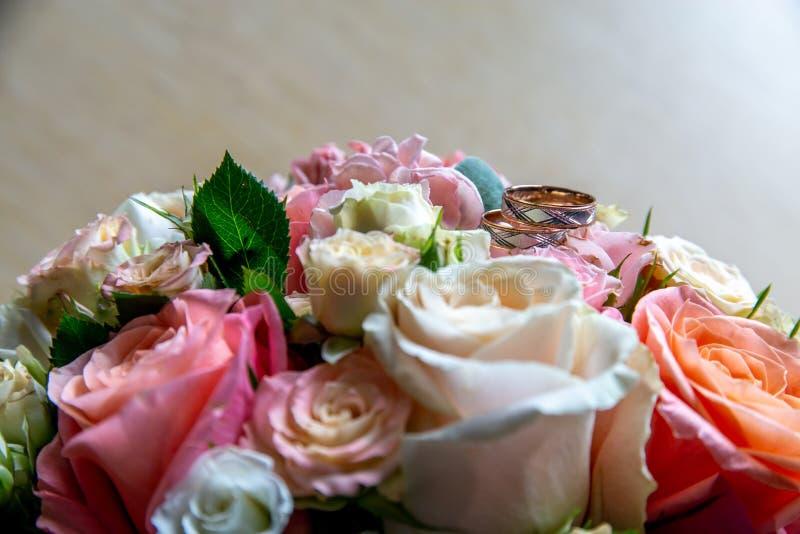 Ramo de novia con las rosas y los anillos de bodas del oro fotografía de archivo