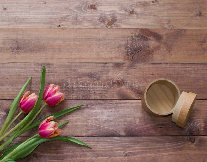 Ramo de Pascua de la primavera de Flatlay de flores del tulip?n con la caja vac?a de madera en fondo de madera Visi?n con el espa imagen de archivo libre de regalías