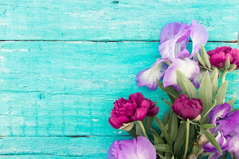 Ramo de peonía y de iris rojos en backgro de madera rústico de la turquesa fotos de archivo