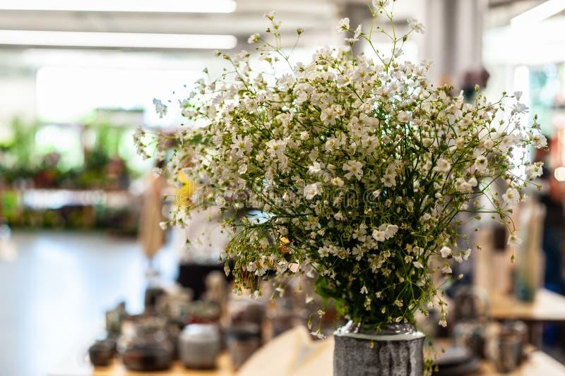 Ramo de pequeñas flores blancas en algunas estancias del florero en espacio interior grande con los temas confusos en fondo borro foto de archivo