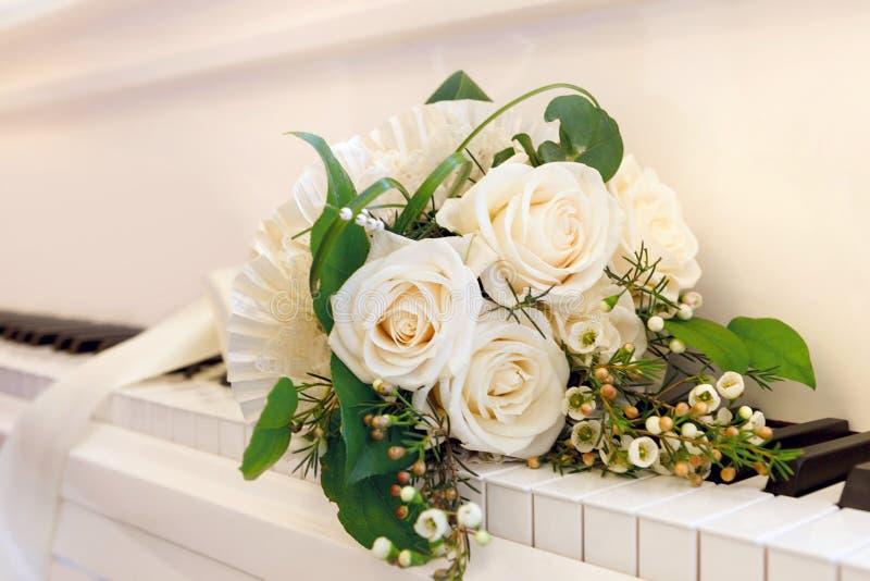 Ramo de rosas blancas que mienten en las llaves del pian magnífico blanco fotos de archivo