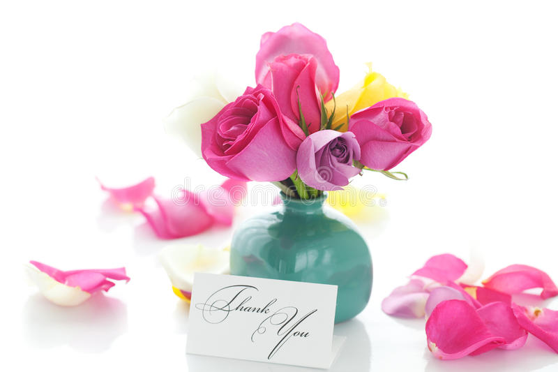 Ramo de rosas coloridas en florero, pétalos y tarjeta imagenes de archivo