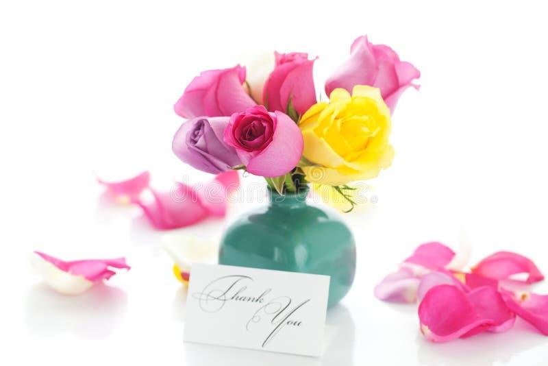 Ramo de rosas coloridas en florero, pétalos y tarjeta foto de archivo libre de regalías