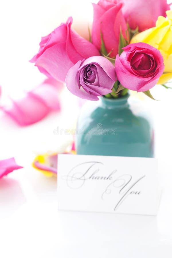 Ramo de rosas coloridas en florero, pétalos y tarjeta fotografía de archivo libre de regalías
