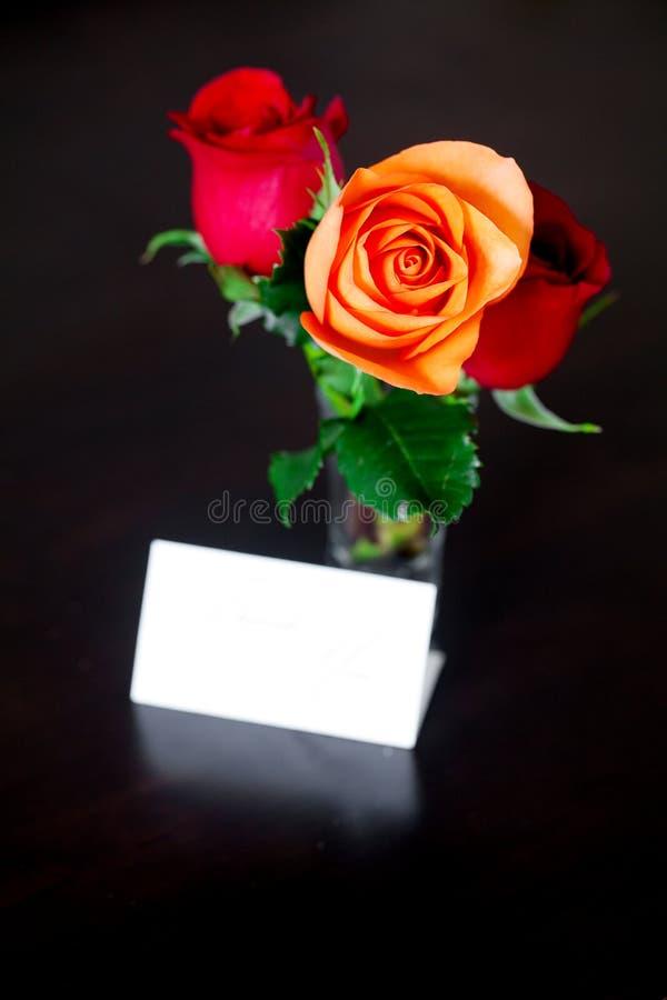 Ramo de rosas coloridas en un florero y una tarjeta foto de archivo libre de regalías