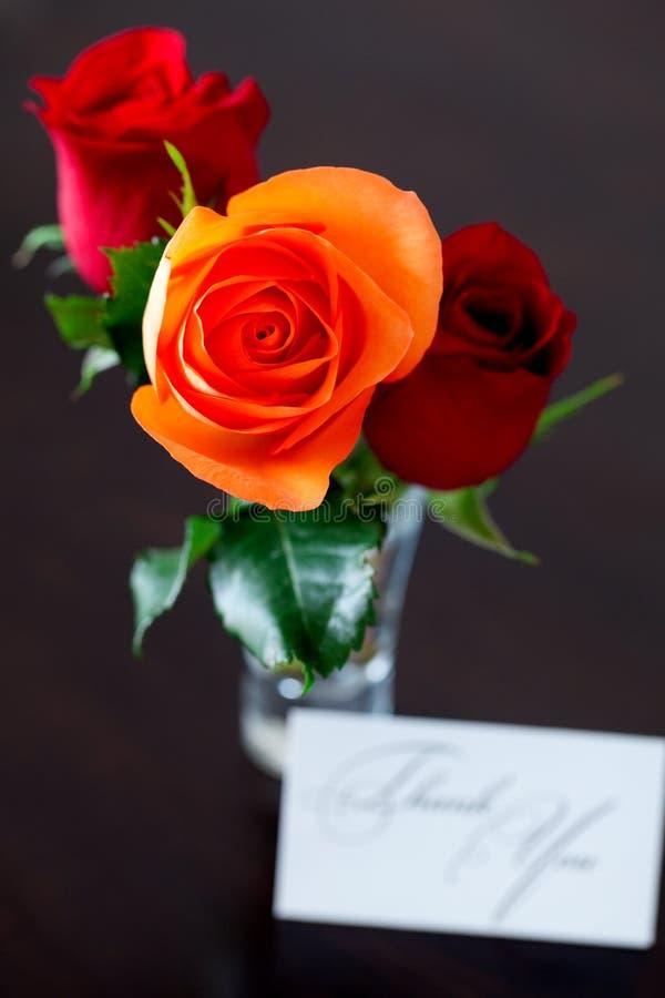 Ramo de rosas coloridas en un florero y una tarjeta imagen de archivo libre de regalías