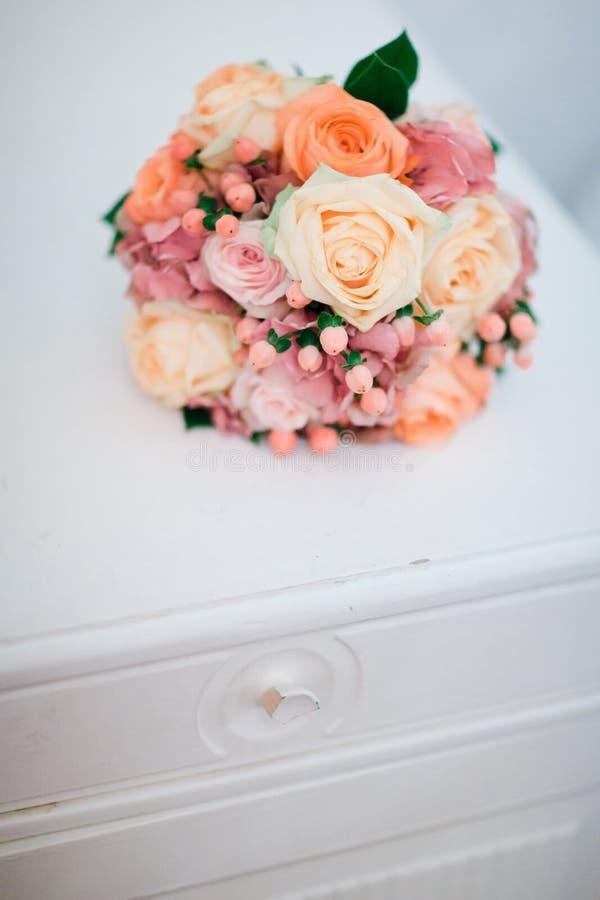 Ramo de rosas en cómoda del vintage imagenes de archivo