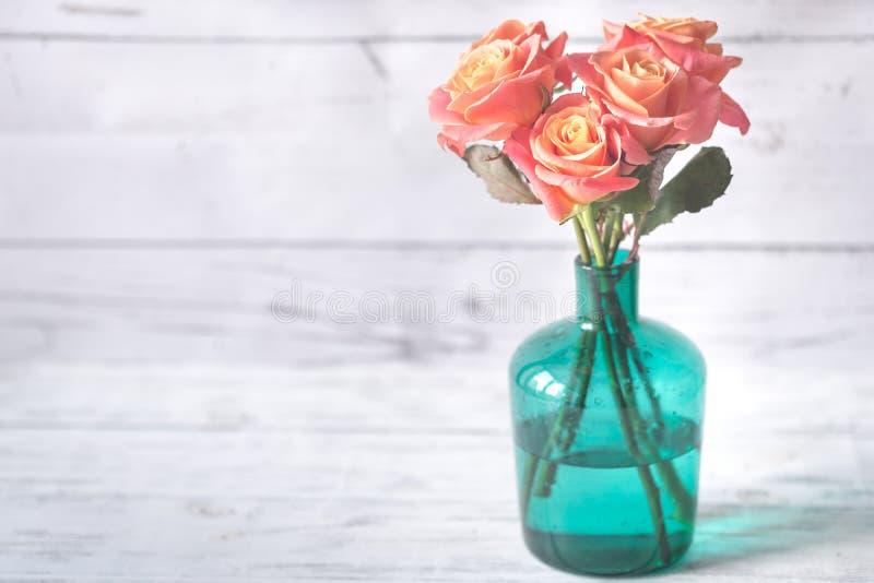 Ramo de rosas en el florero en el fondo de madera imagen de archivo