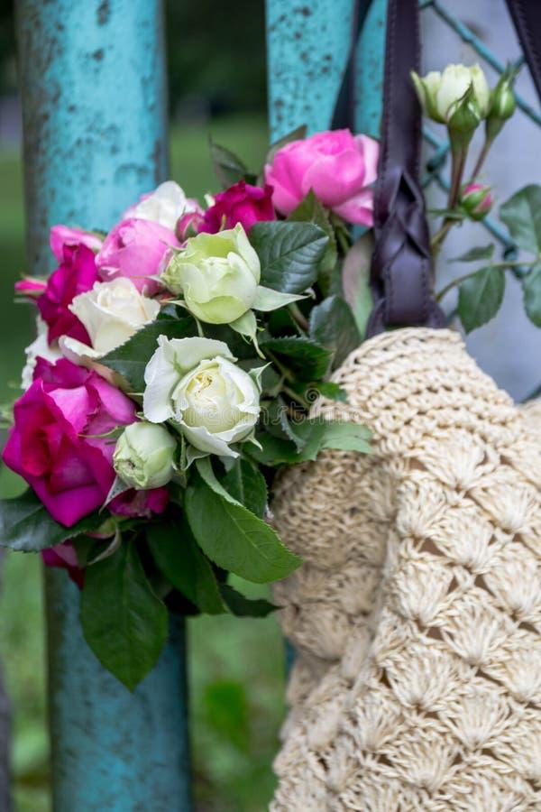 Ramo de rosas inglesas fragantes del rosa y blancas en un bolso de la rafia que cuelga en la cerca imagen de archivo