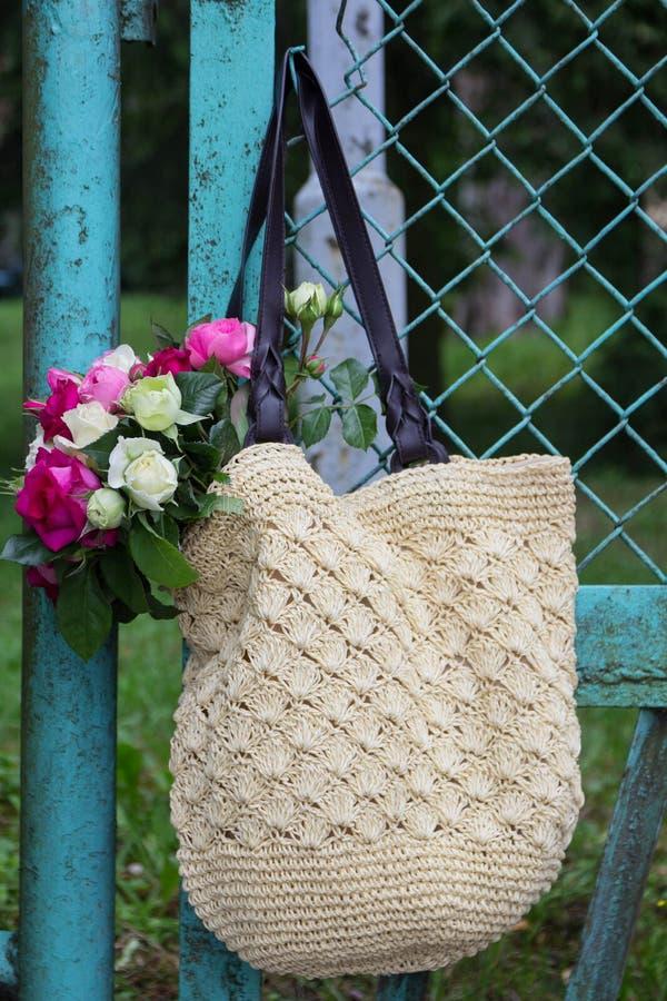 Ramo de rosas inglesas fragantes del rosa y blancas en un bolso de la rafia que cuelga en la cerca imagenes de archivo
