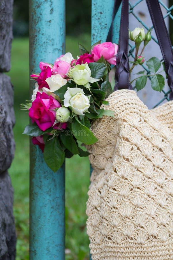 Ramo de rosas inglesas fragantes del rosa y blancas en un bolso de la rafia que cuelga en la cerca fotografía de archivo